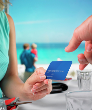 Woman handing credit card to server at beach
