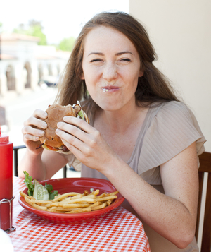 Woman eating burger with food on her mouth