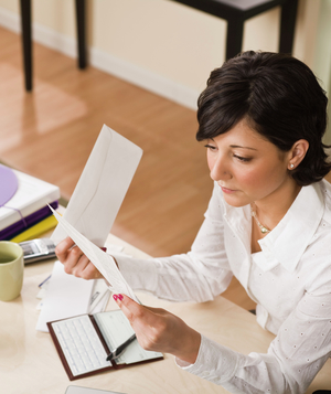 Woman at desk with checkbook and paperwork