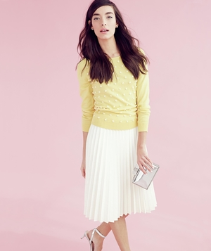 Model wearing yellow sweater and pleated white skirt