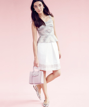 Model wearing peplum top with white skirt and pink bag