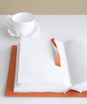 Paper construction of open book with cup and saucer by Matthew Sporzynski