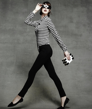 Model wearing houndstooth top and slim black trousers