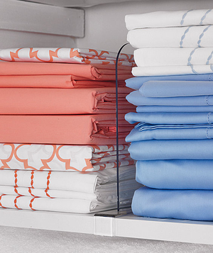 Linen closet organized with clear plastic dividers