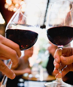 Hands holding glasses of red wine in restaurant