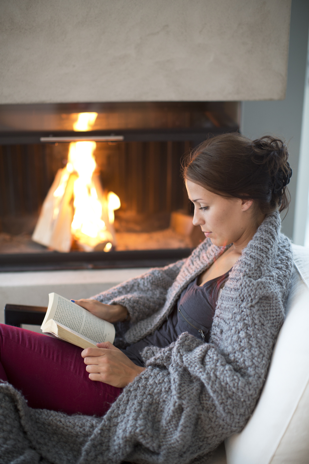 woman cozy reading book by fire