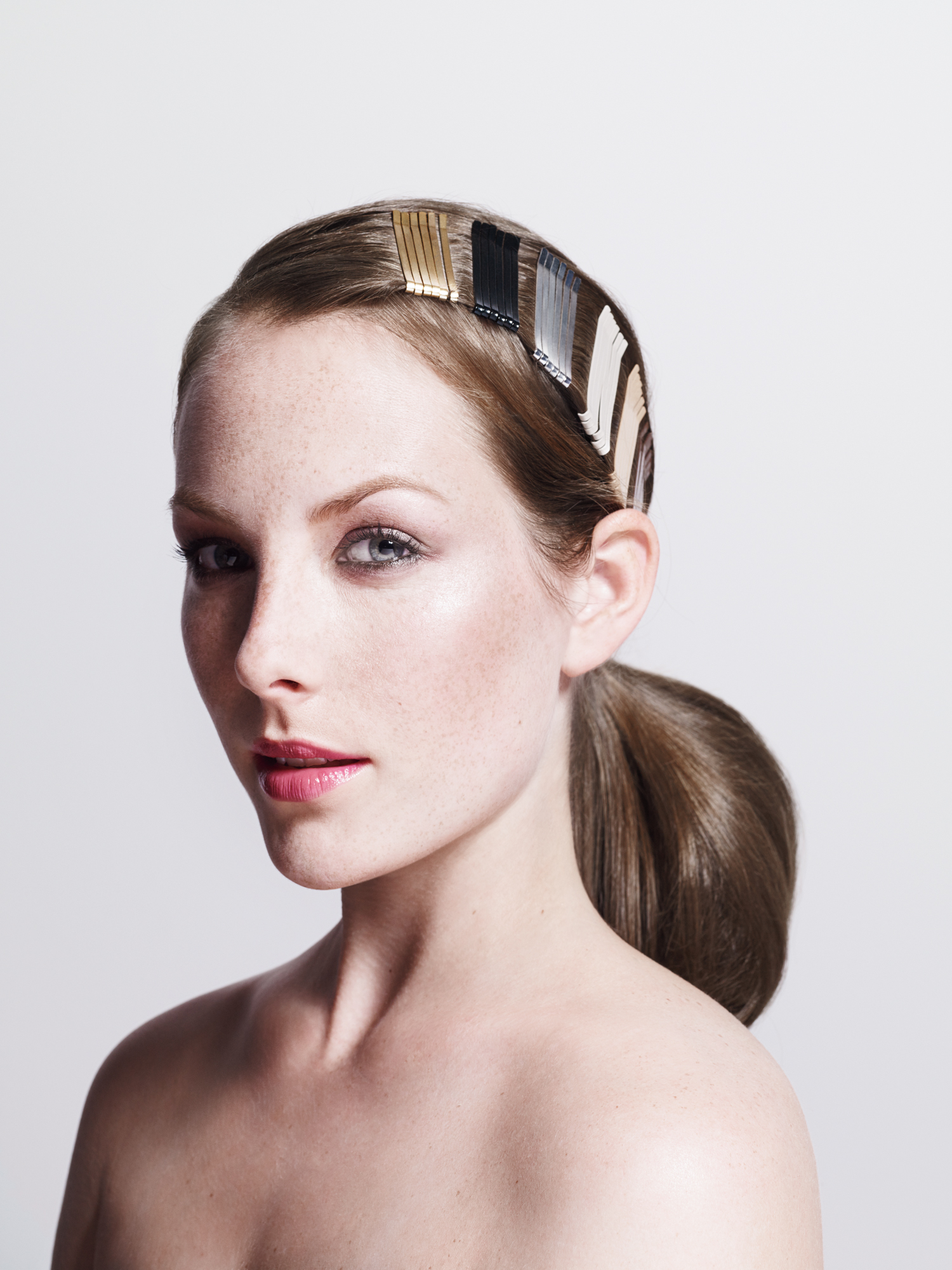 Model with bands of different-colored bobby pins