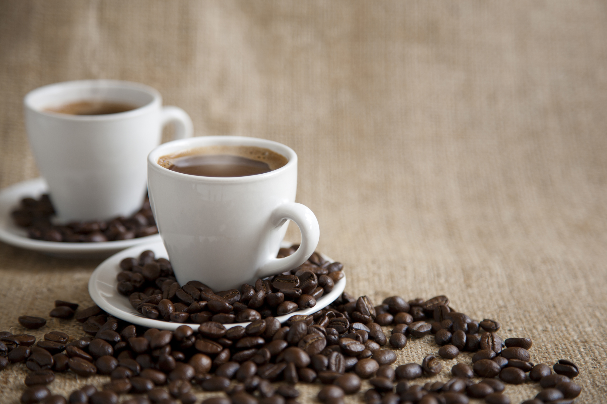 Coffee cups and saucers with coffee beans