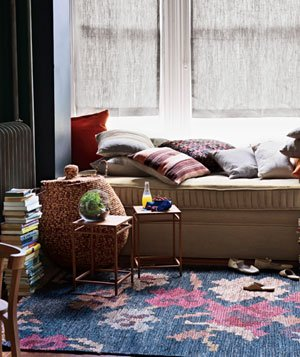 Room with pillows, daybed, books, basket, rug