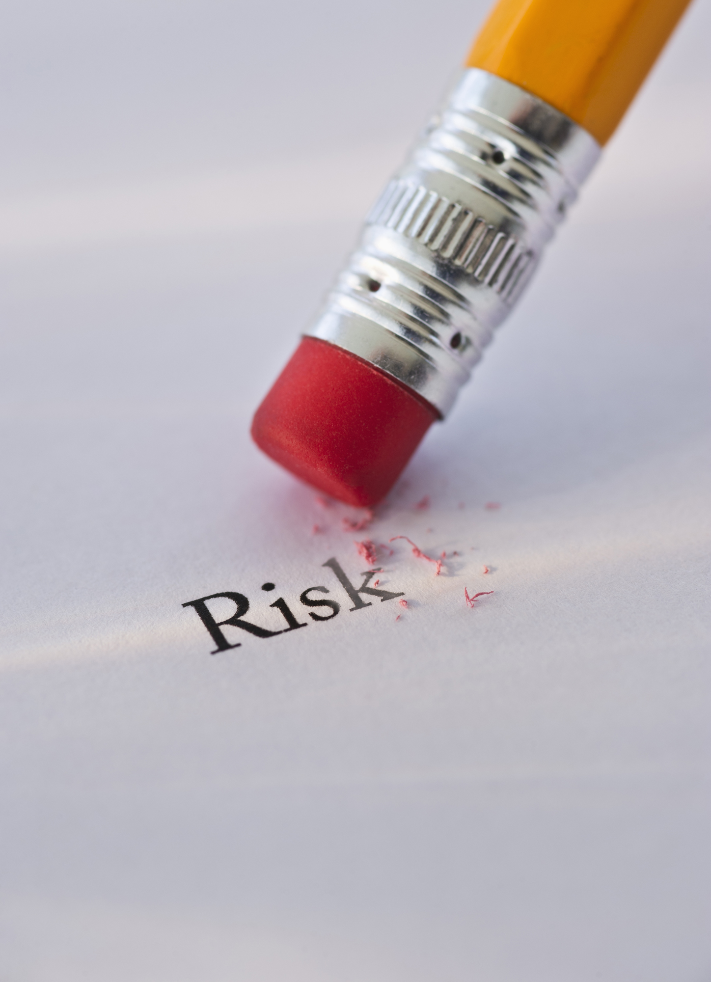 Pencil erasing the word risk