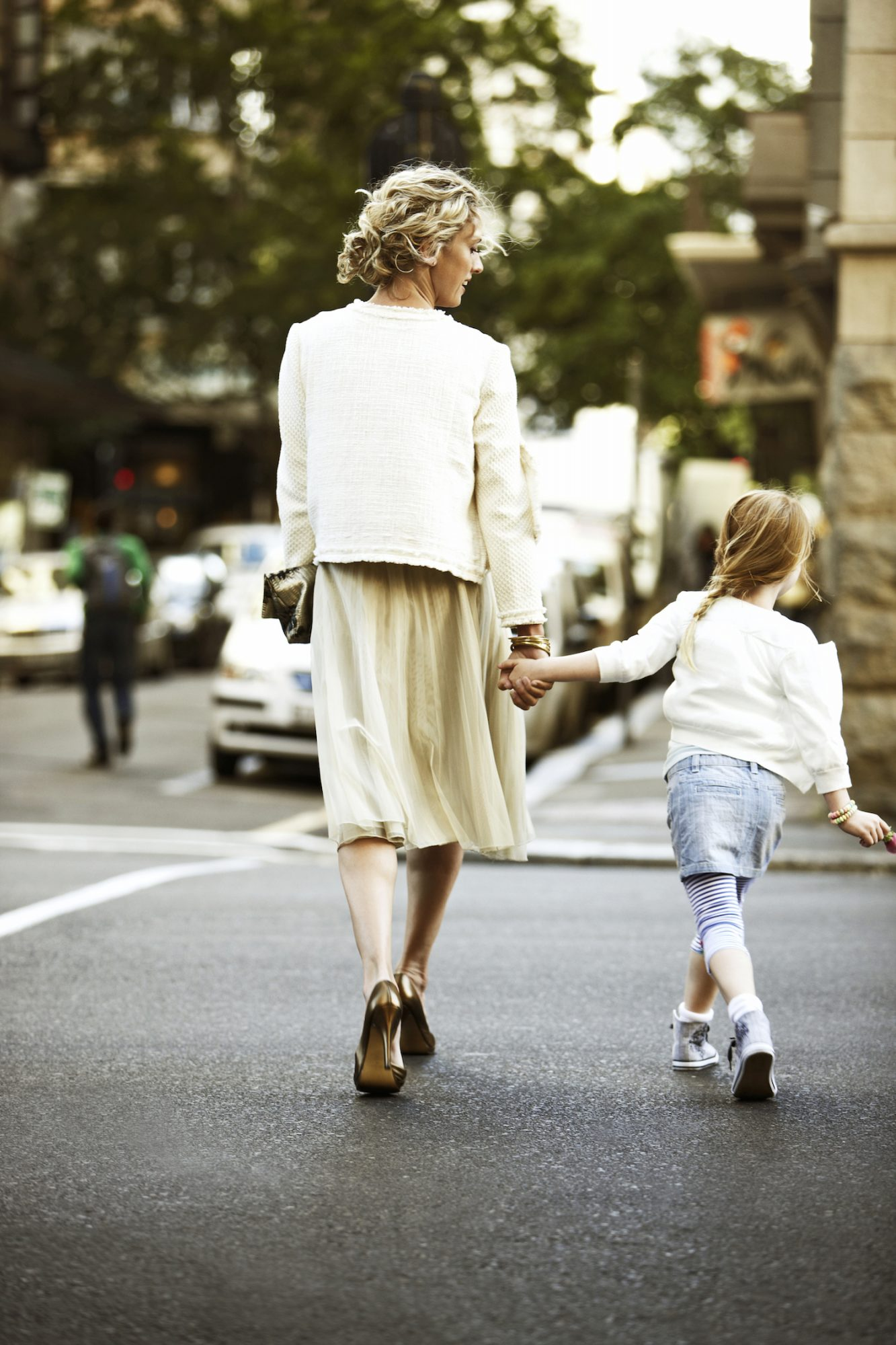 mother and daughter crossing street holding hands