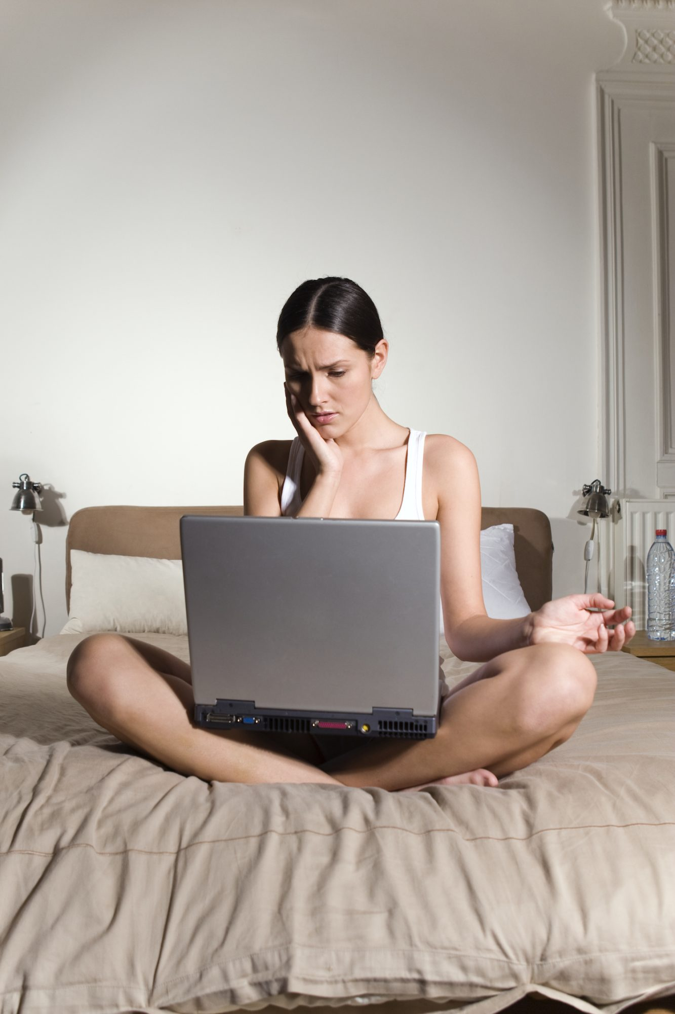 women nervous stressed on computer in bed