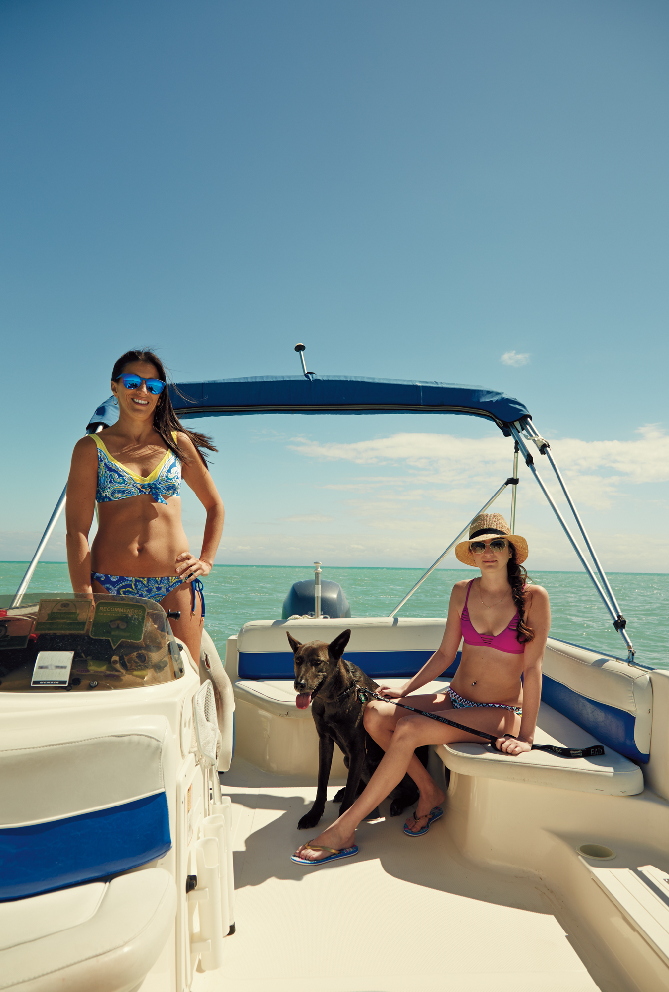 Models in swimsuits with dog on speedboat