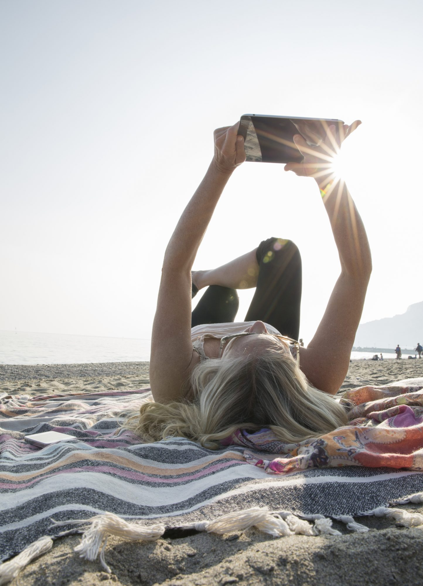 girl reading on sand at beach