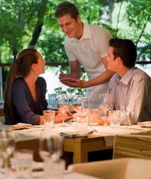 Waiter taking order from couple at restaurant table
