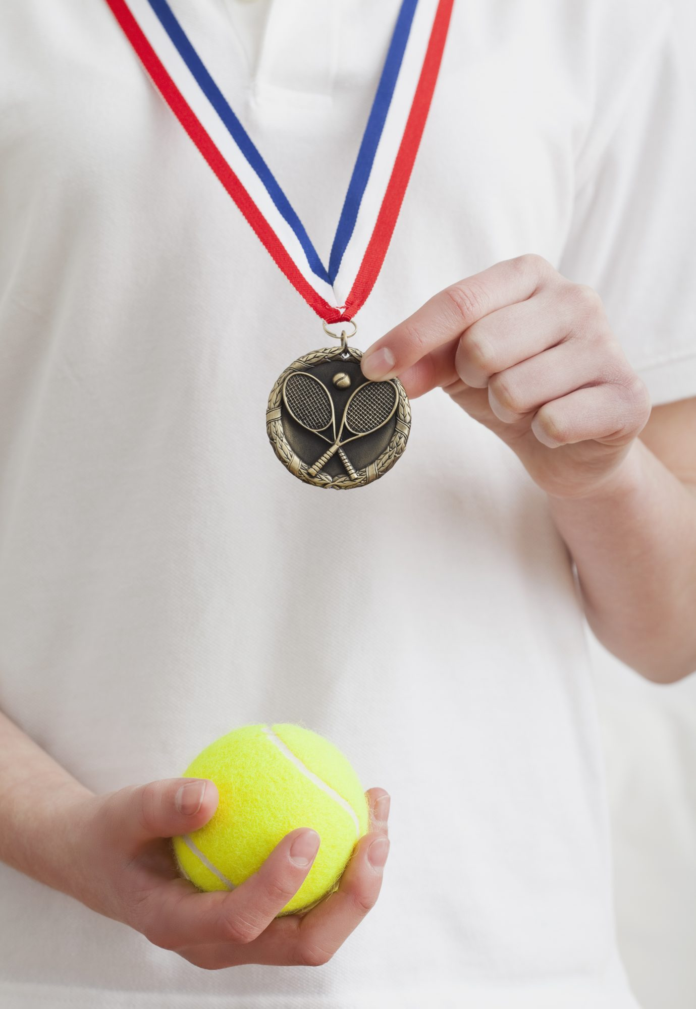 Kid with a medal and a tennis ball.
