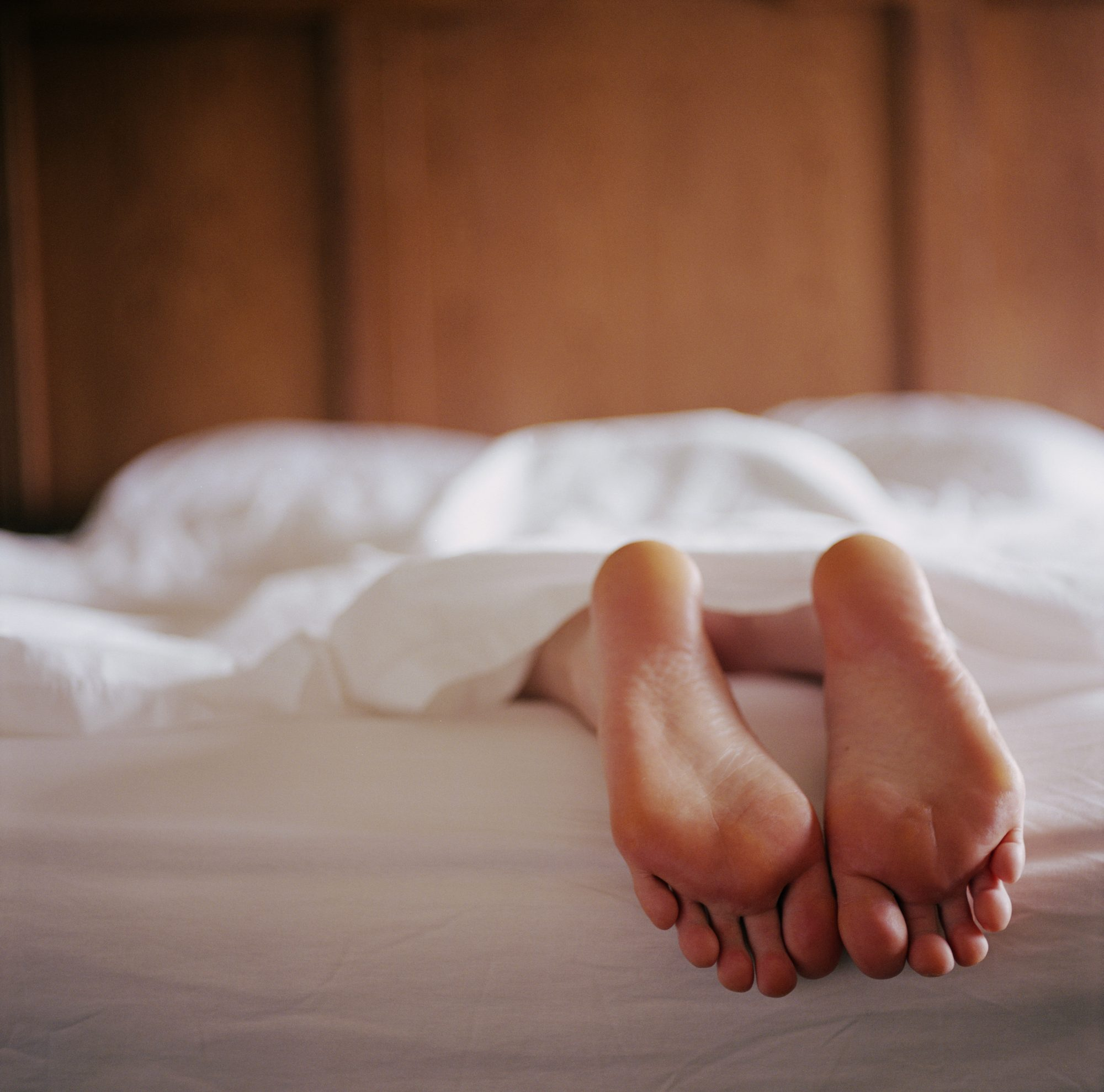 woman sticking foot out of bed