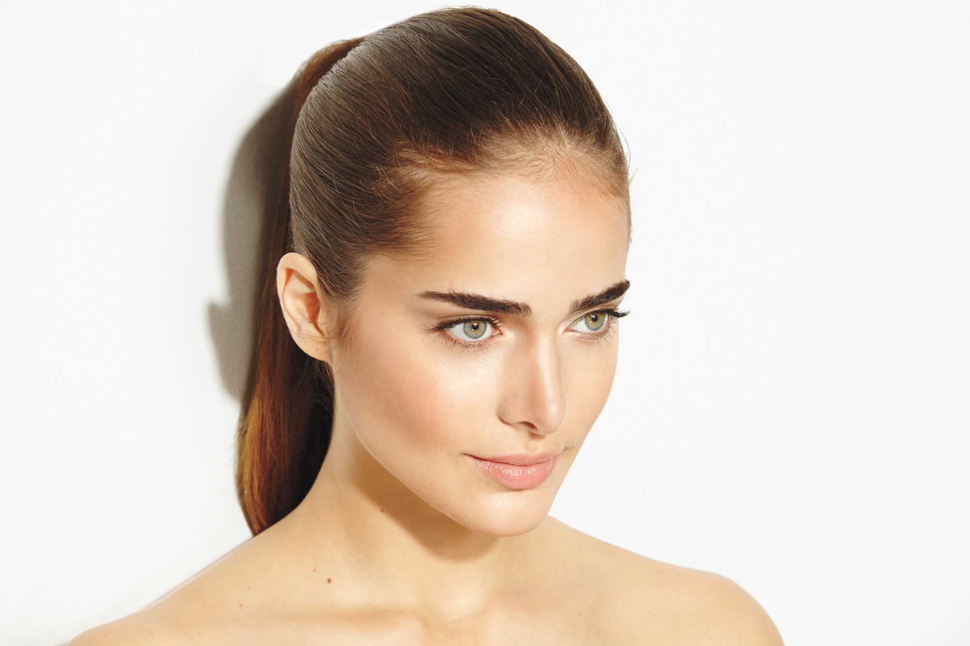 Model with glowing skin and hair pulled back in ponytail