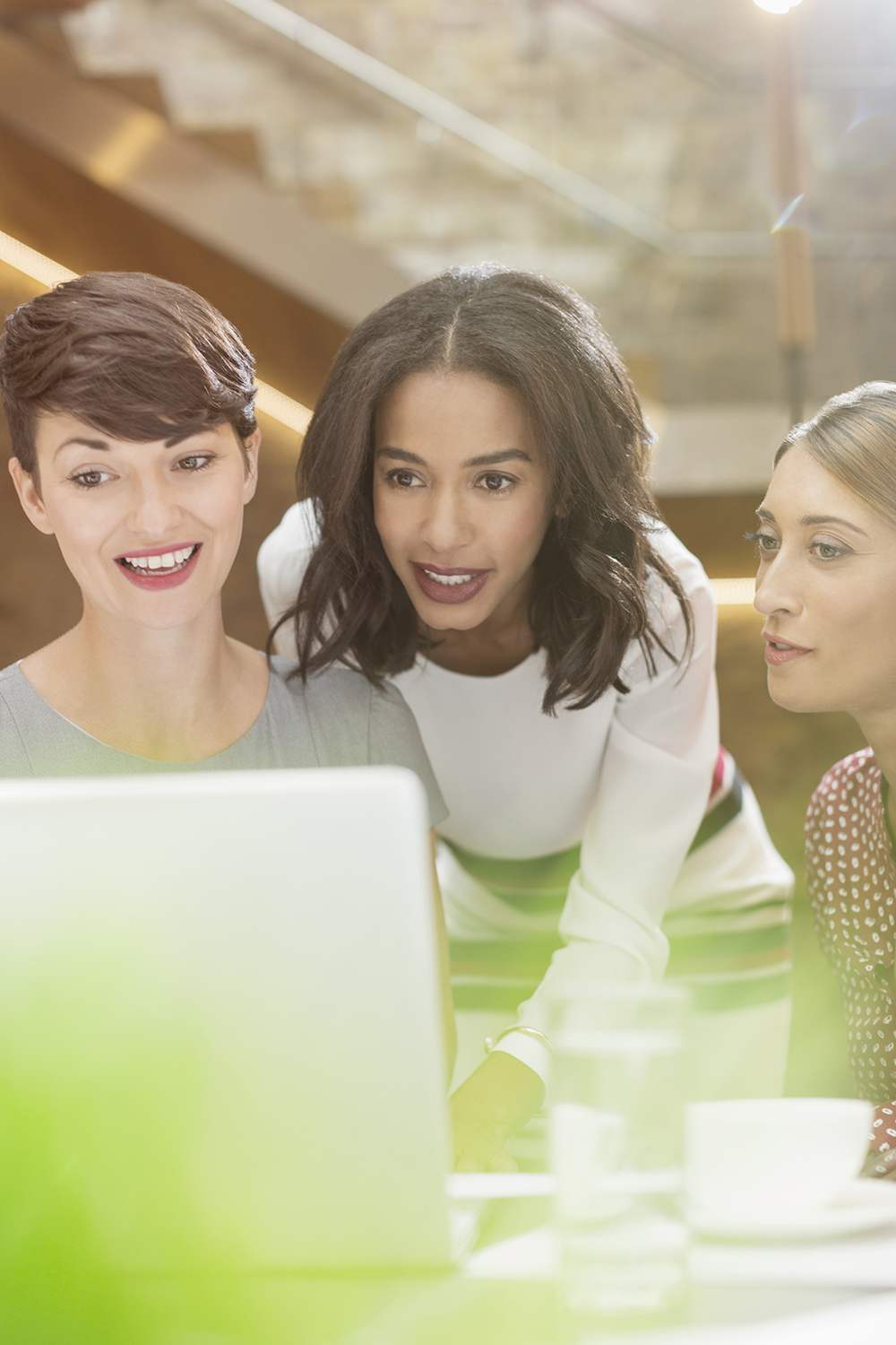 3 women looking at laptop at work