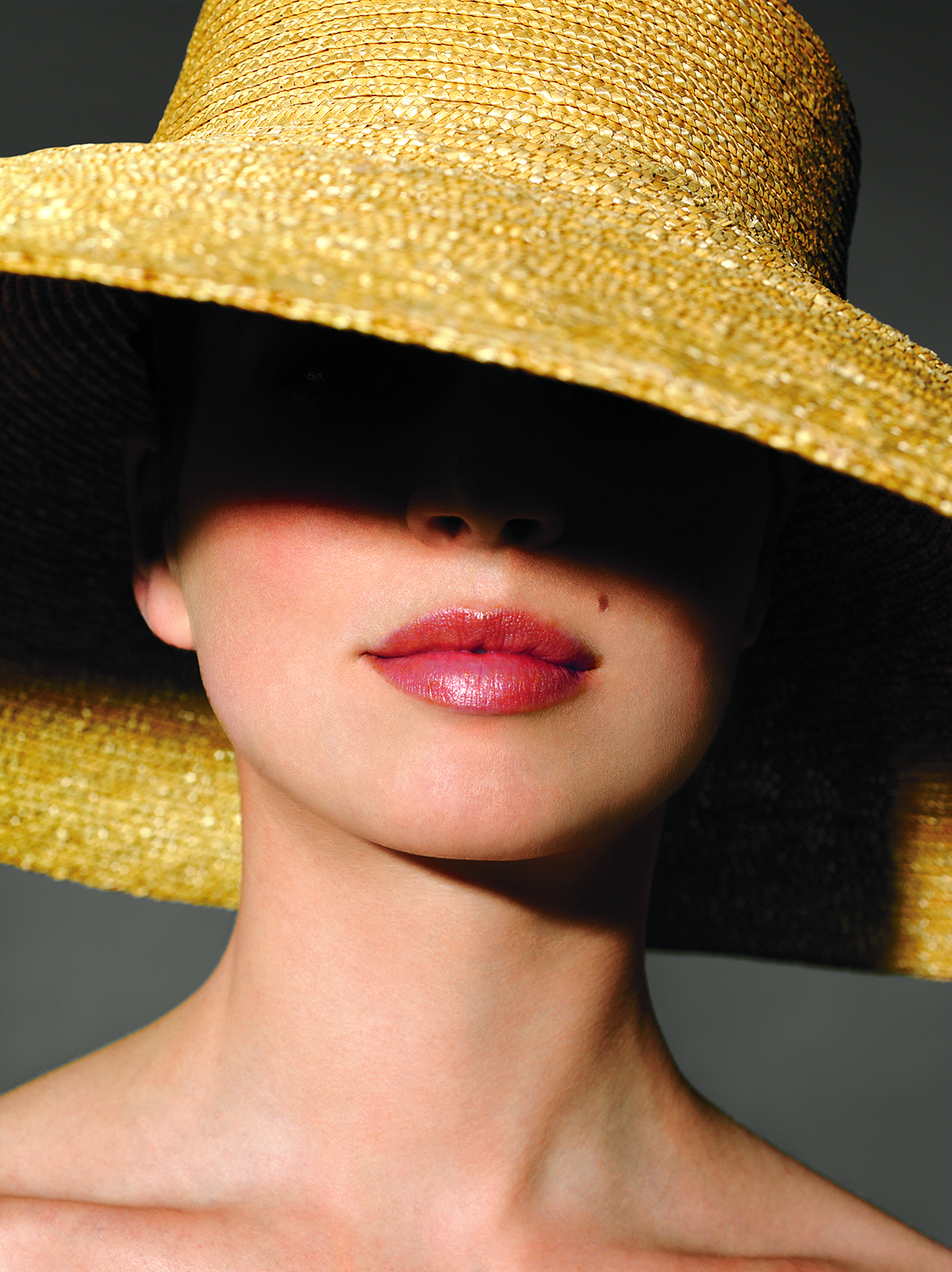 Woman with large straw hat covering her face