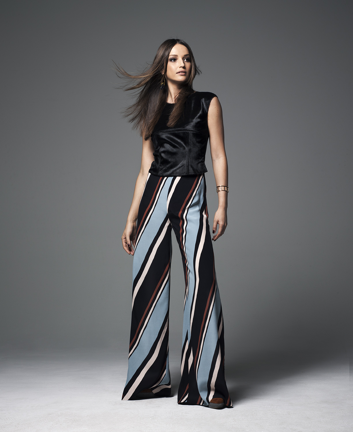 Model wearing black top and striped trousers