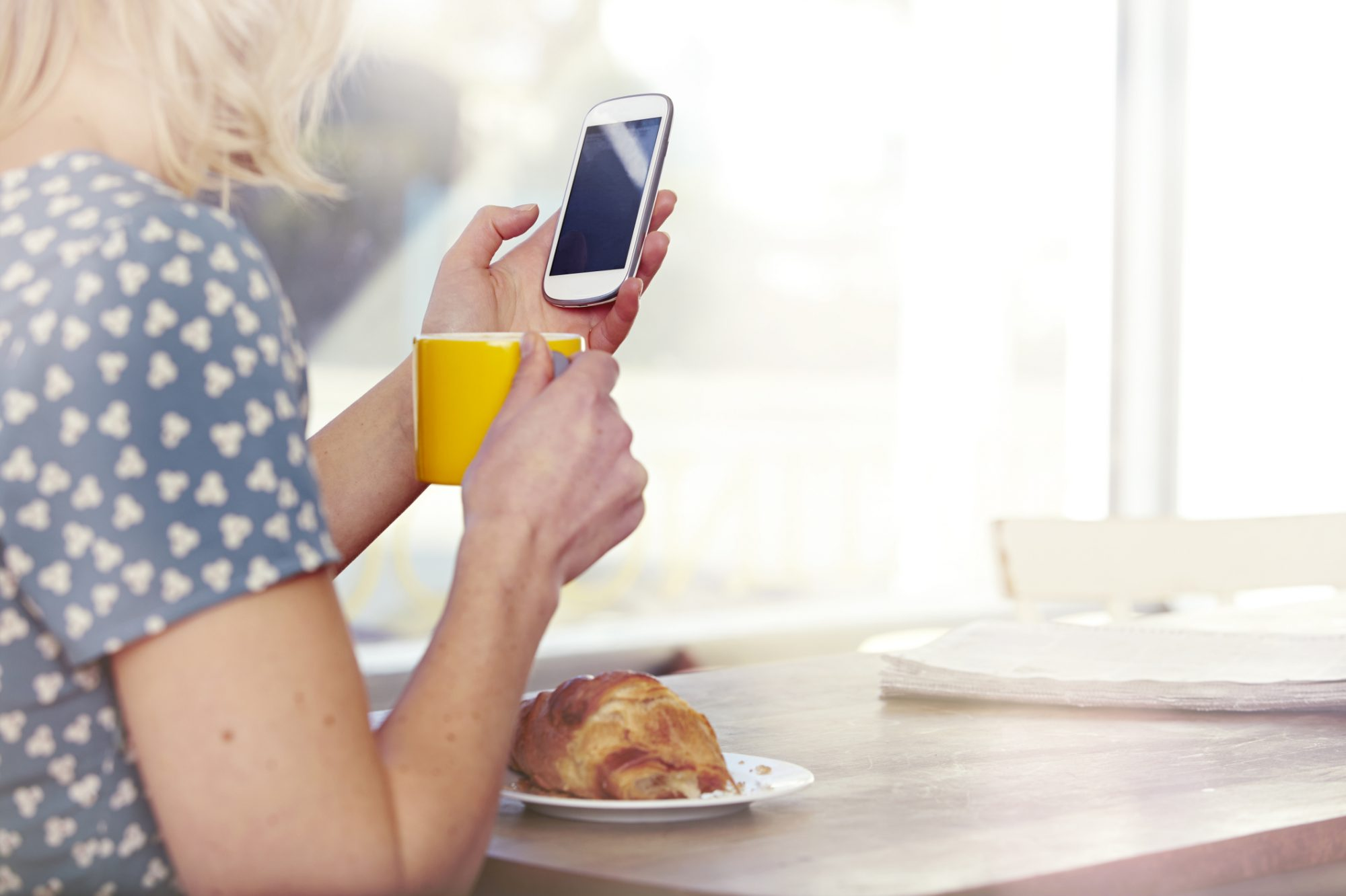 Woman using her phone at the table.