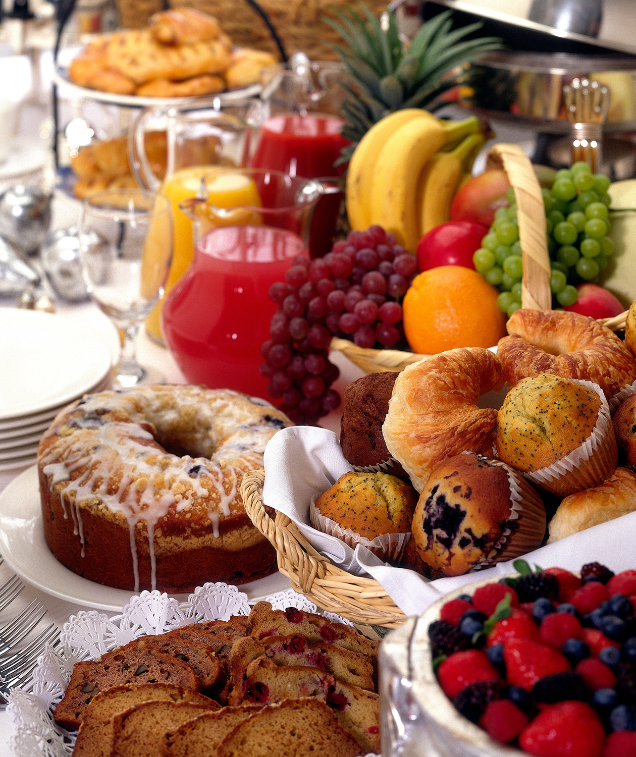 Breakfast buffet with cakes, muffins, fruit, juice