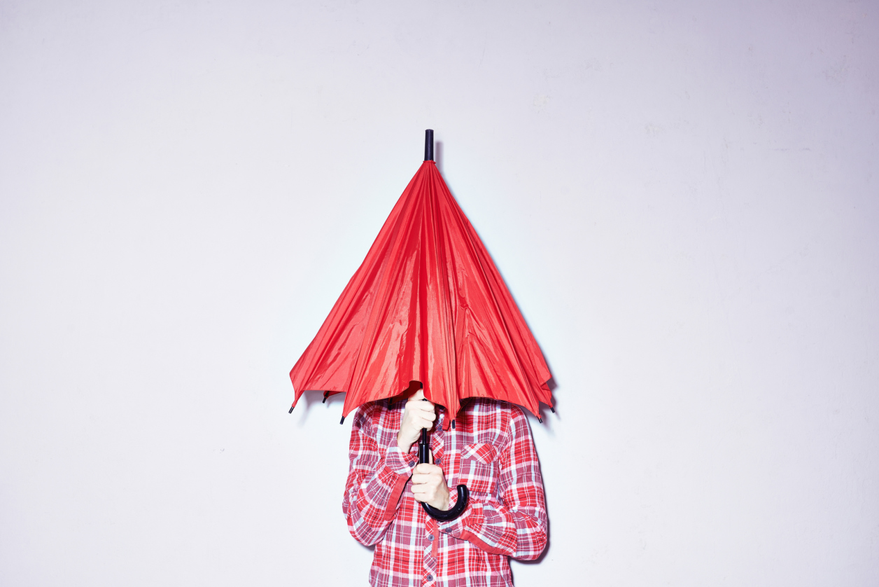 Studio shot of young woman holding red umbrella over her head