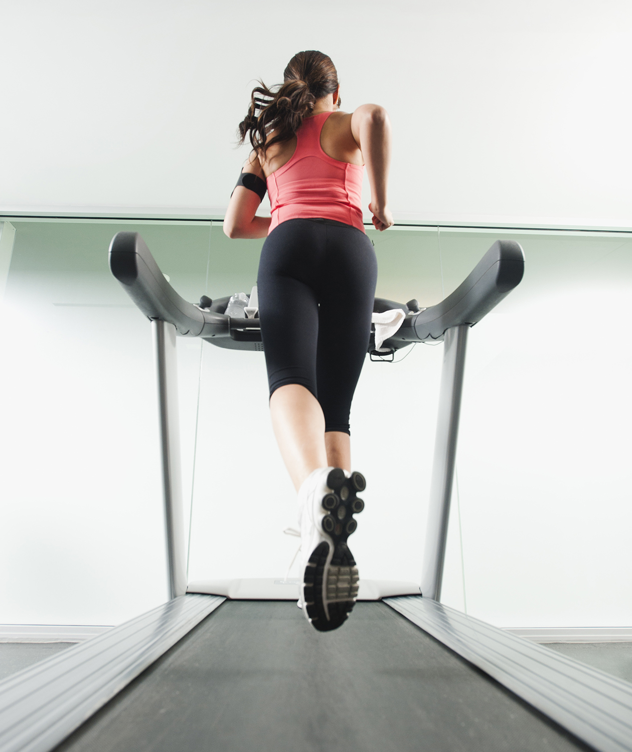 Rear view of woman running on treadmill