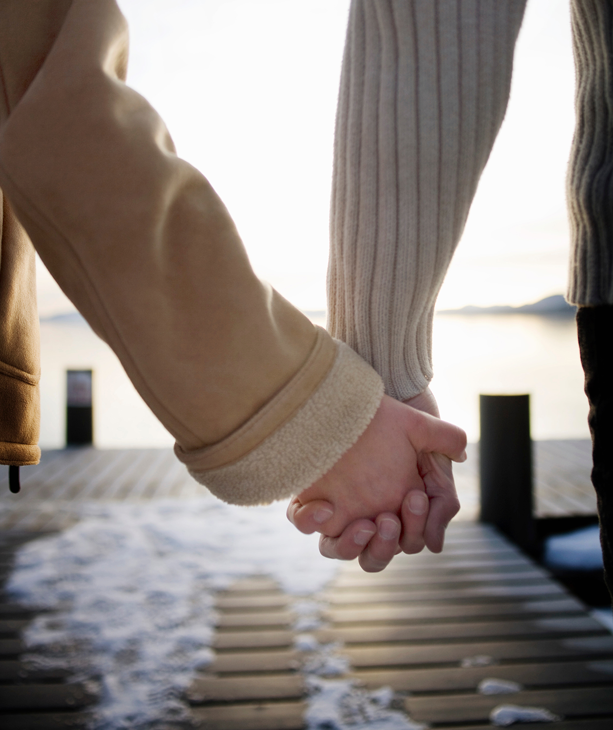 Couple holding hands on a snowy pier