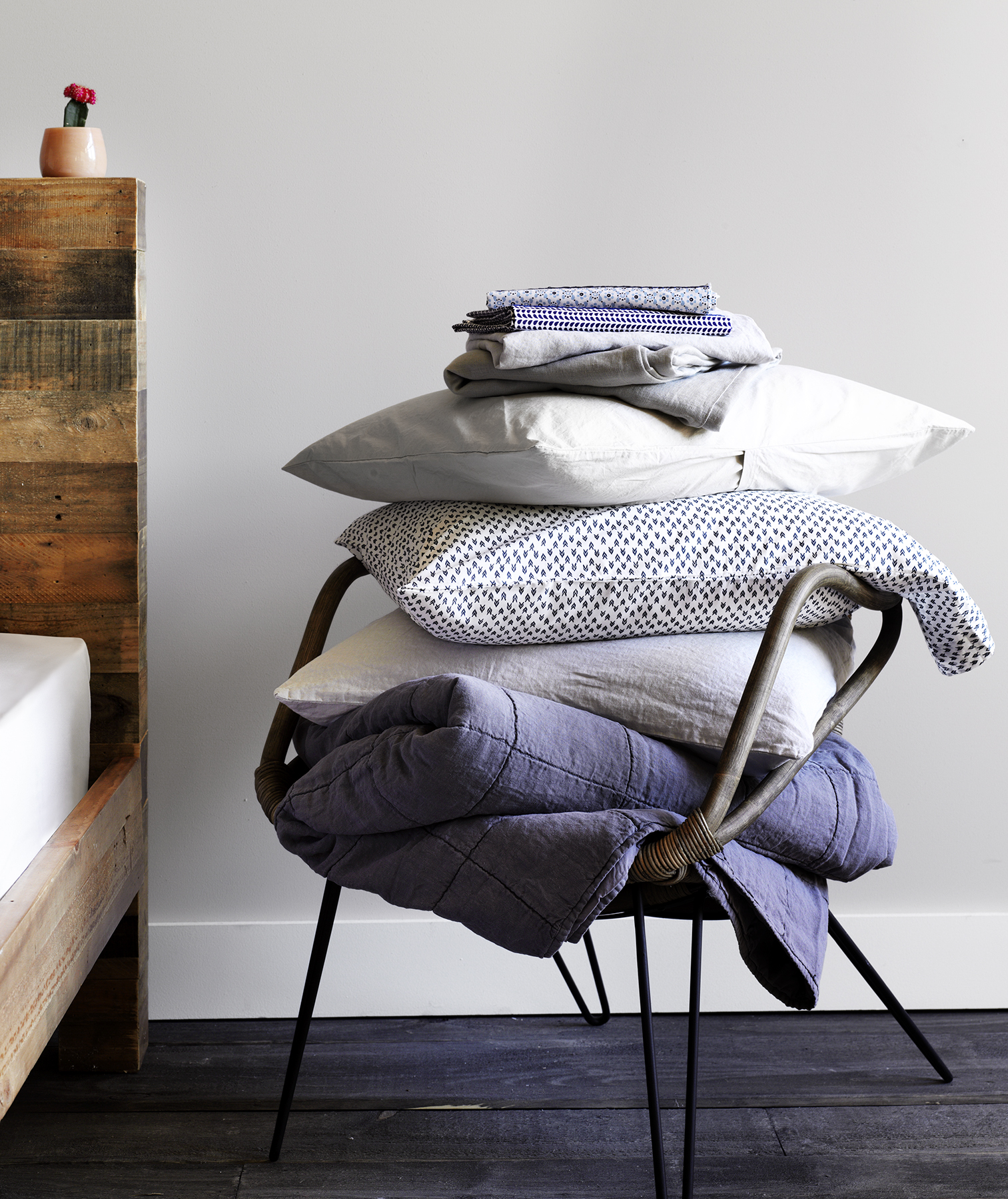 Chair stacked with blue and white bed linens