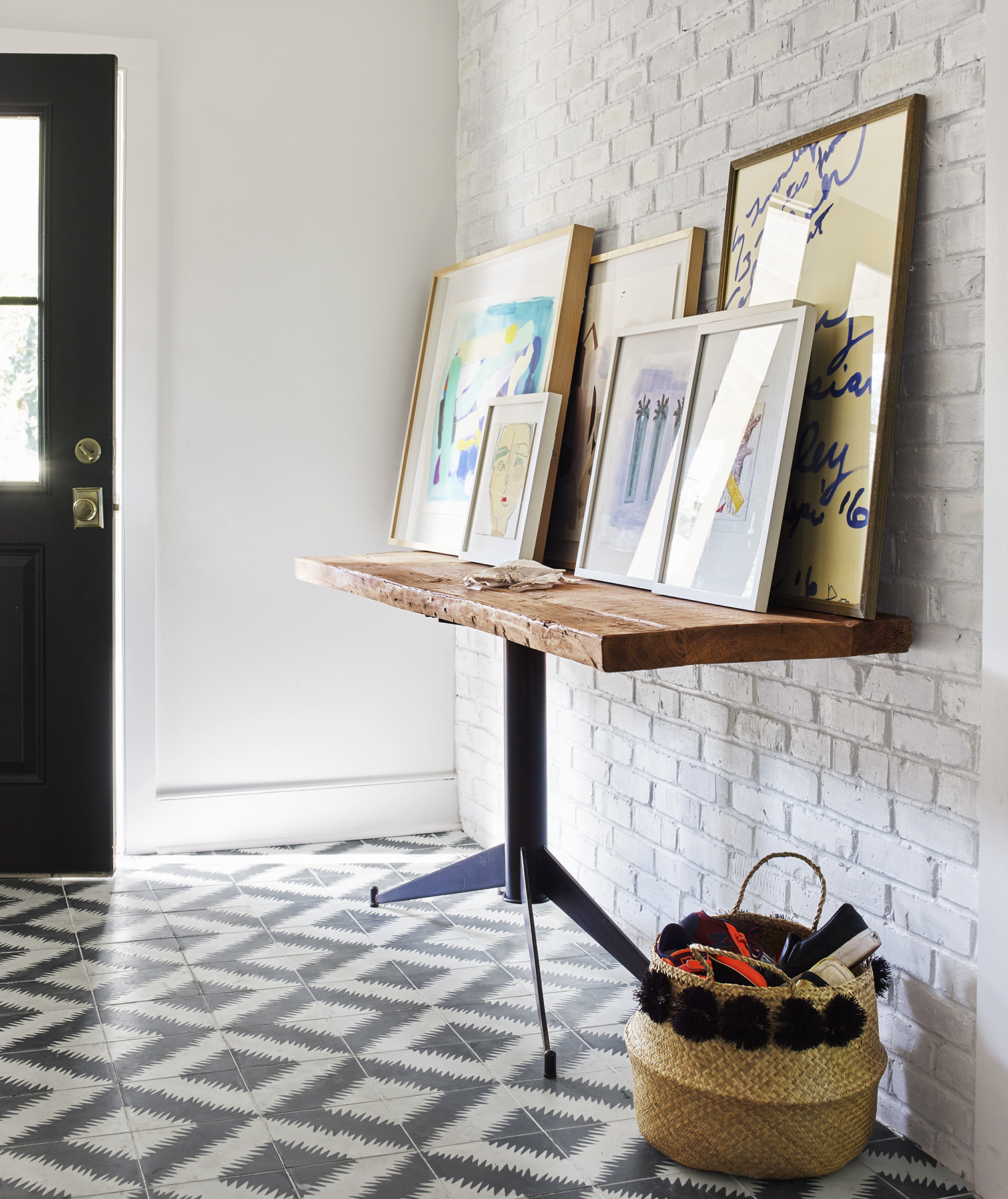 Entryway with patterned tile and white brick wall