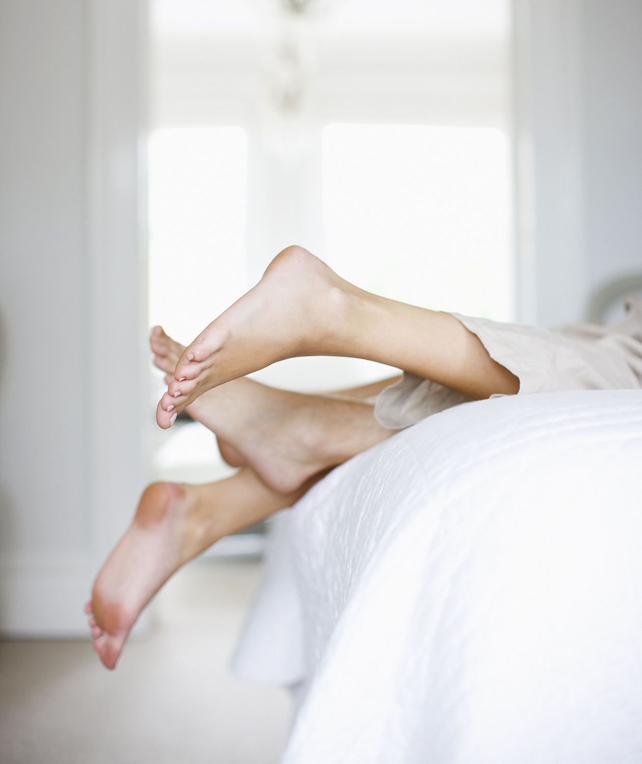 Couple's feet sticking out of the sheets