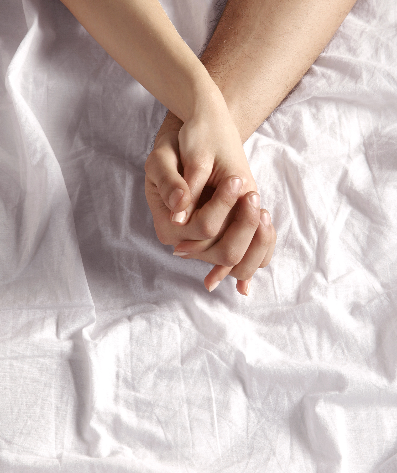 Couple holding hands on sheet