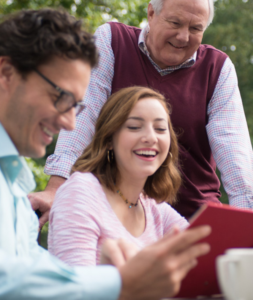family smiling and looking at a photo album