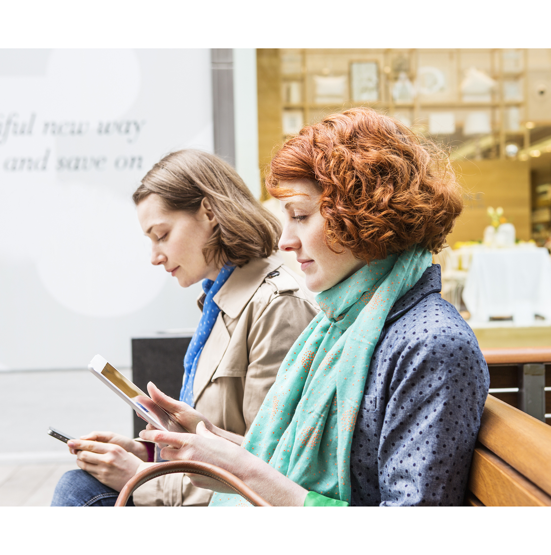 Women sitting looking at phones