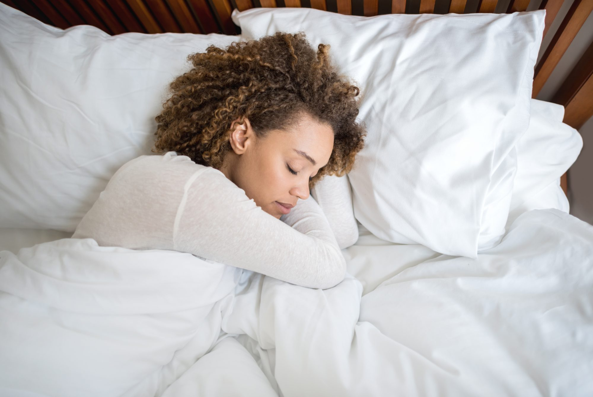 How to Sleep Better: Woman sleeping on white sheets