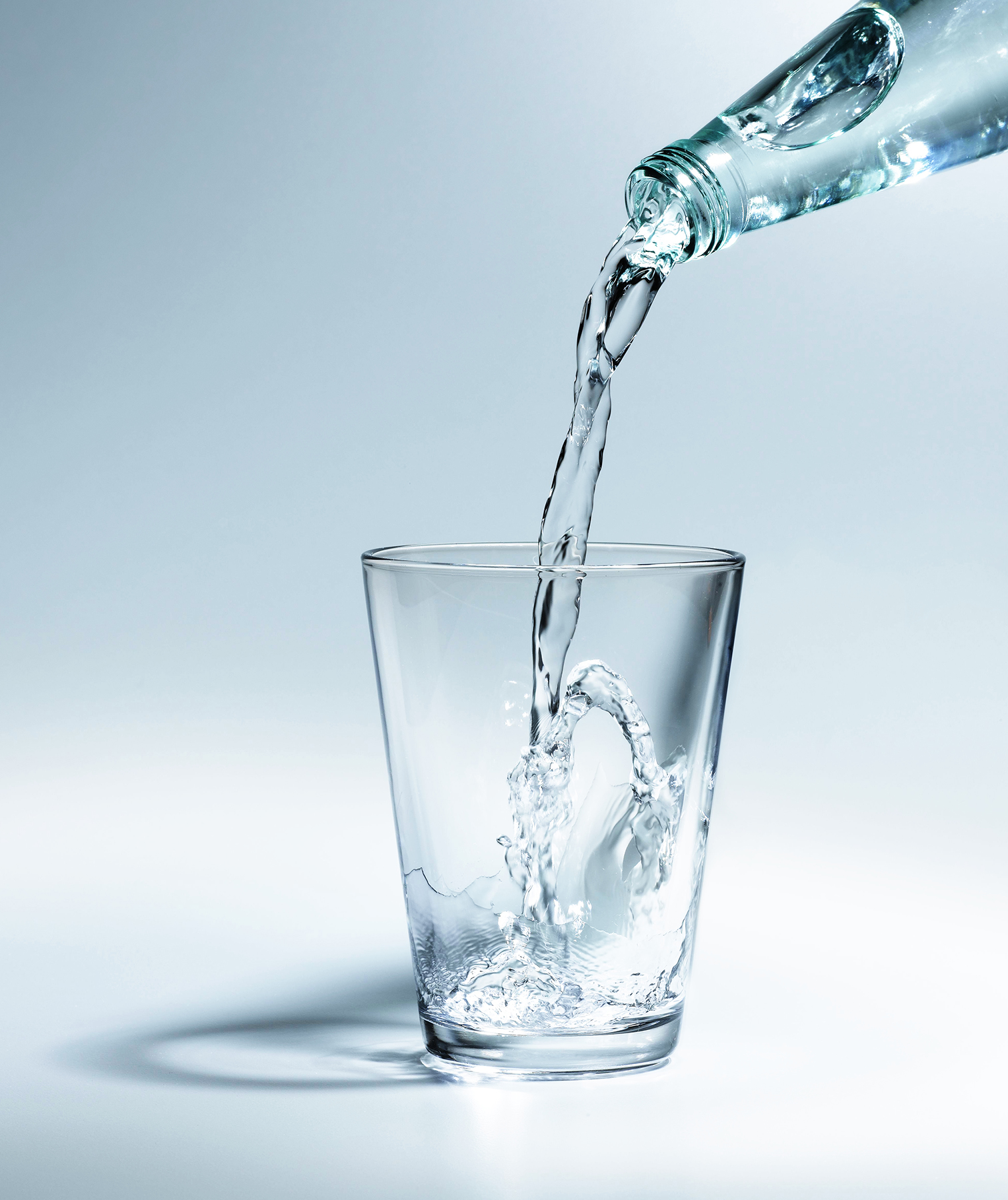 Pouring water out of bottle into glass