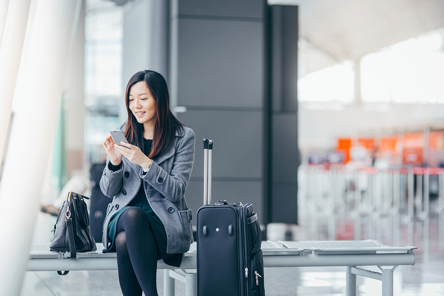Woman Sitting With Suitcase in Airport