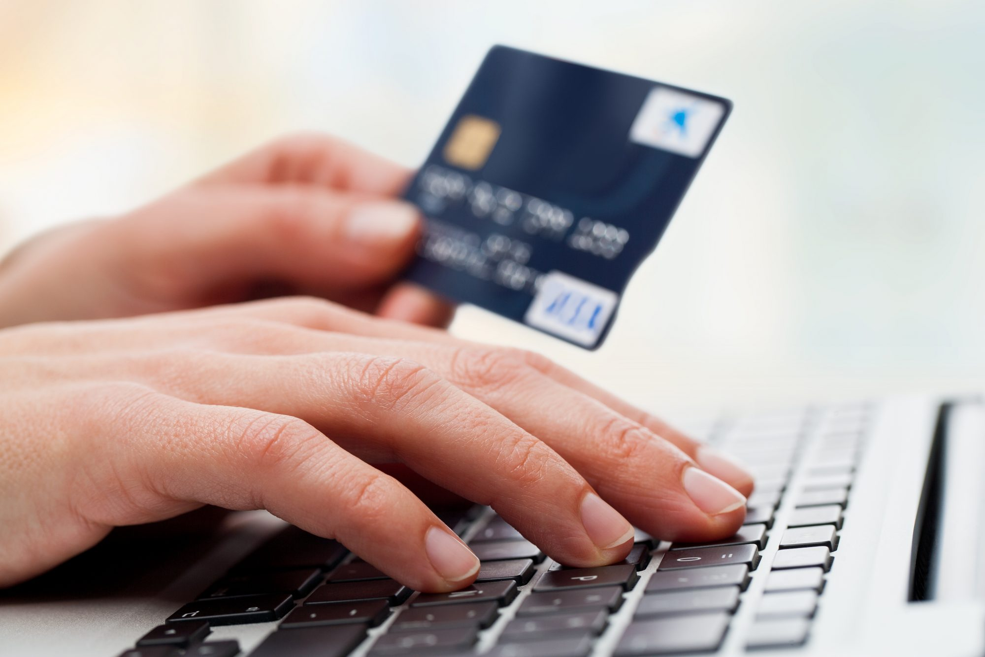 Hand typing on laptop with credit card