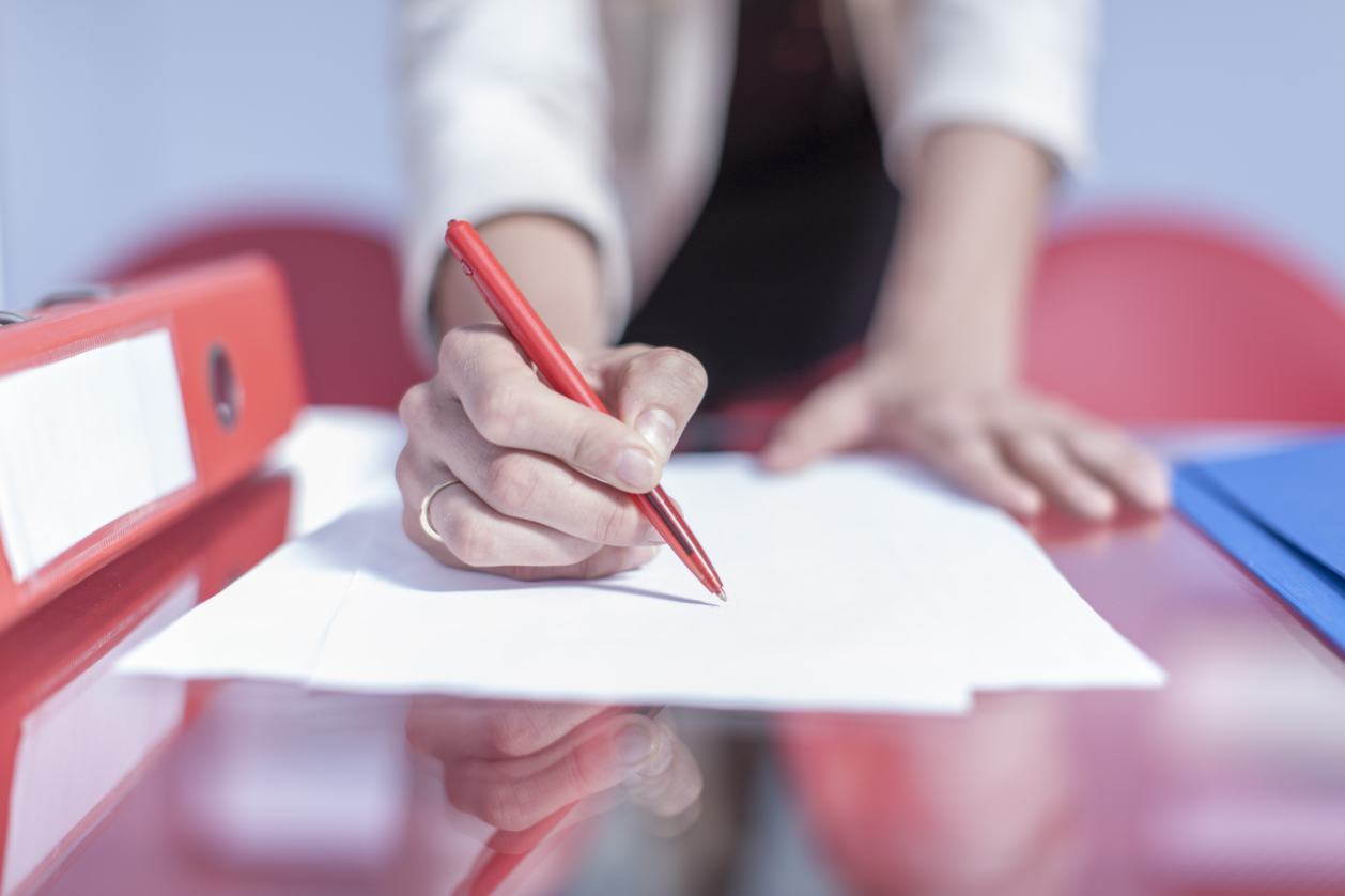 Woman editing with a red pen