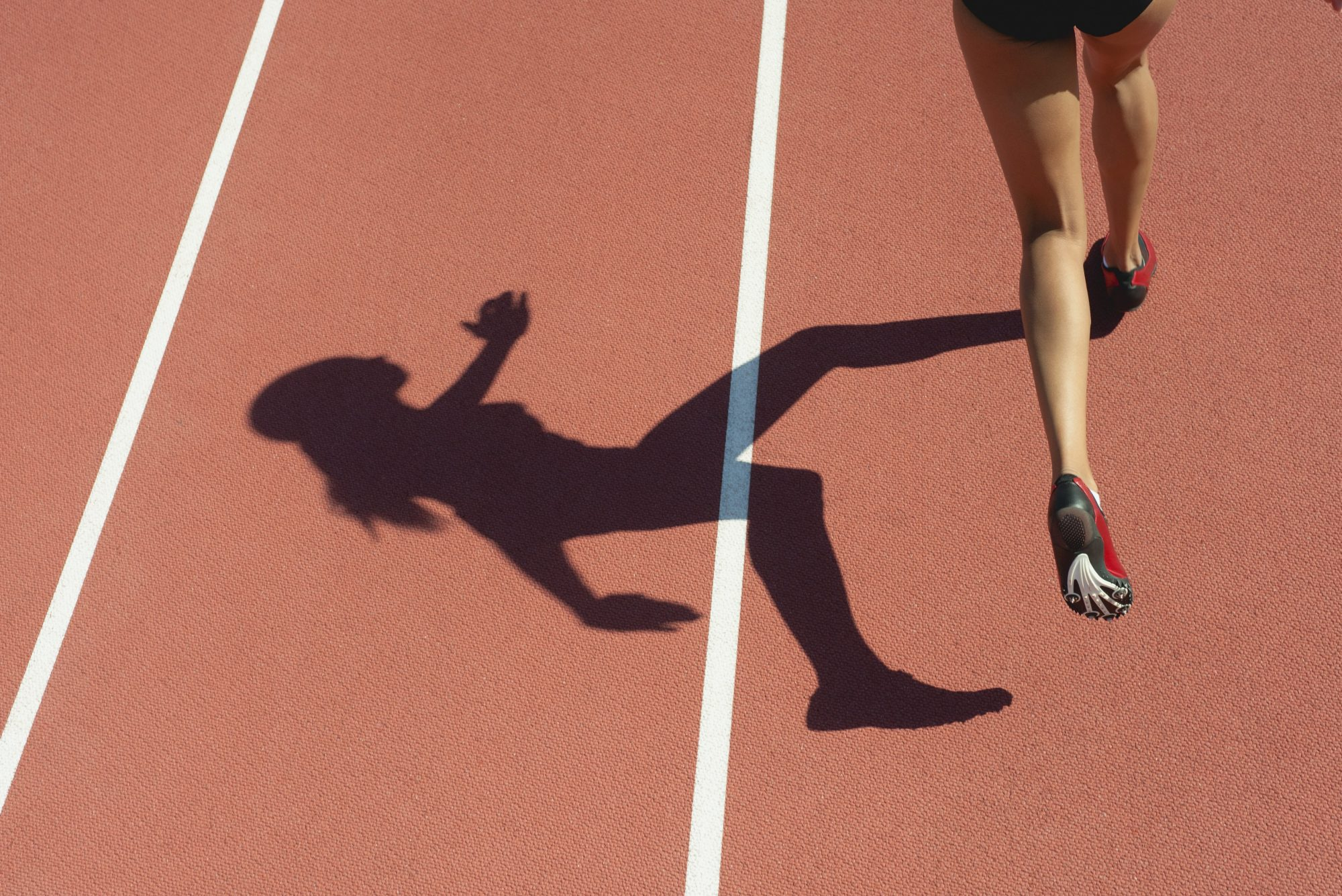 Female athlete running on track, low section, focus on shadow