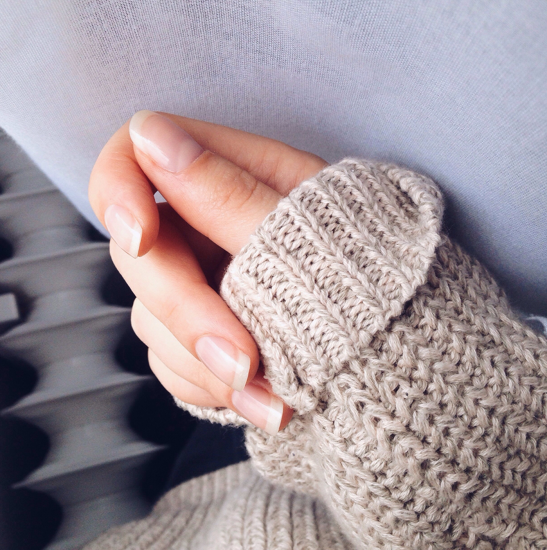 Manicured nails and sweater sleeve