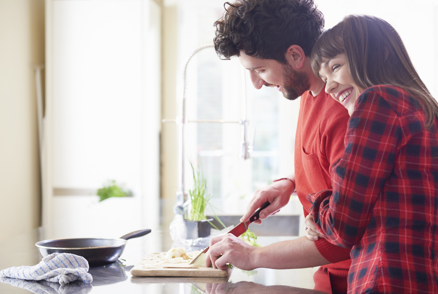 Couple hugging, cooking, in kitchen