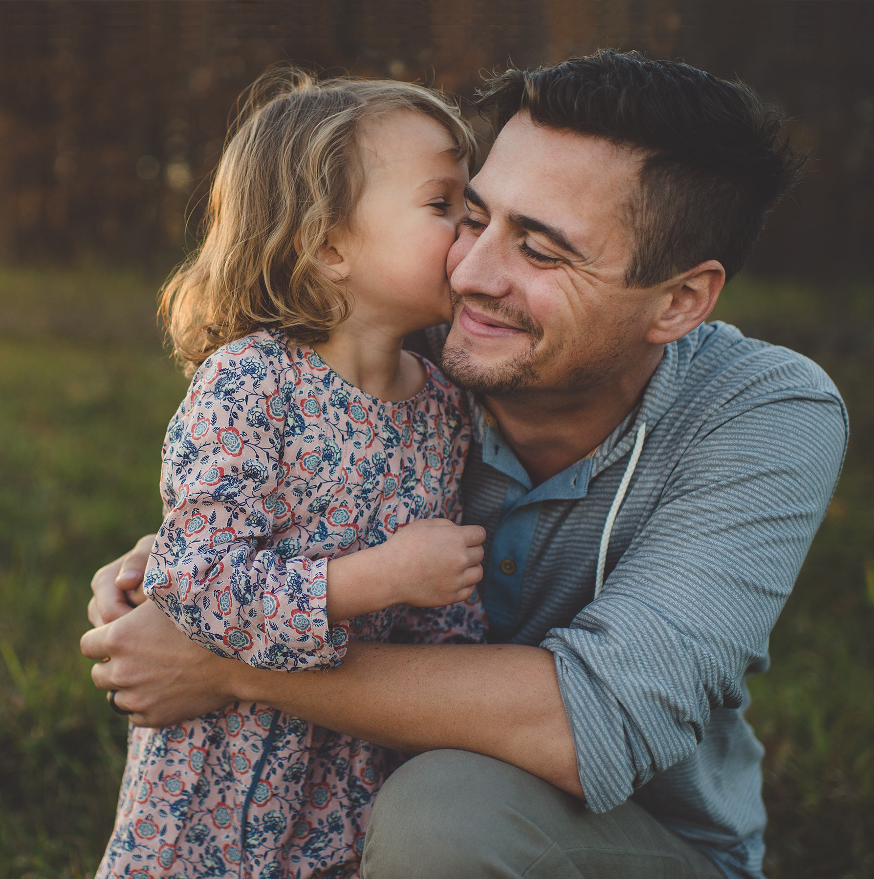 Father and daughter hug in field