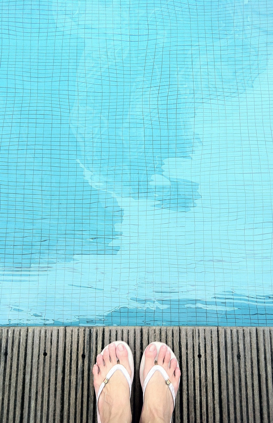 Feet at edge of swimming pool