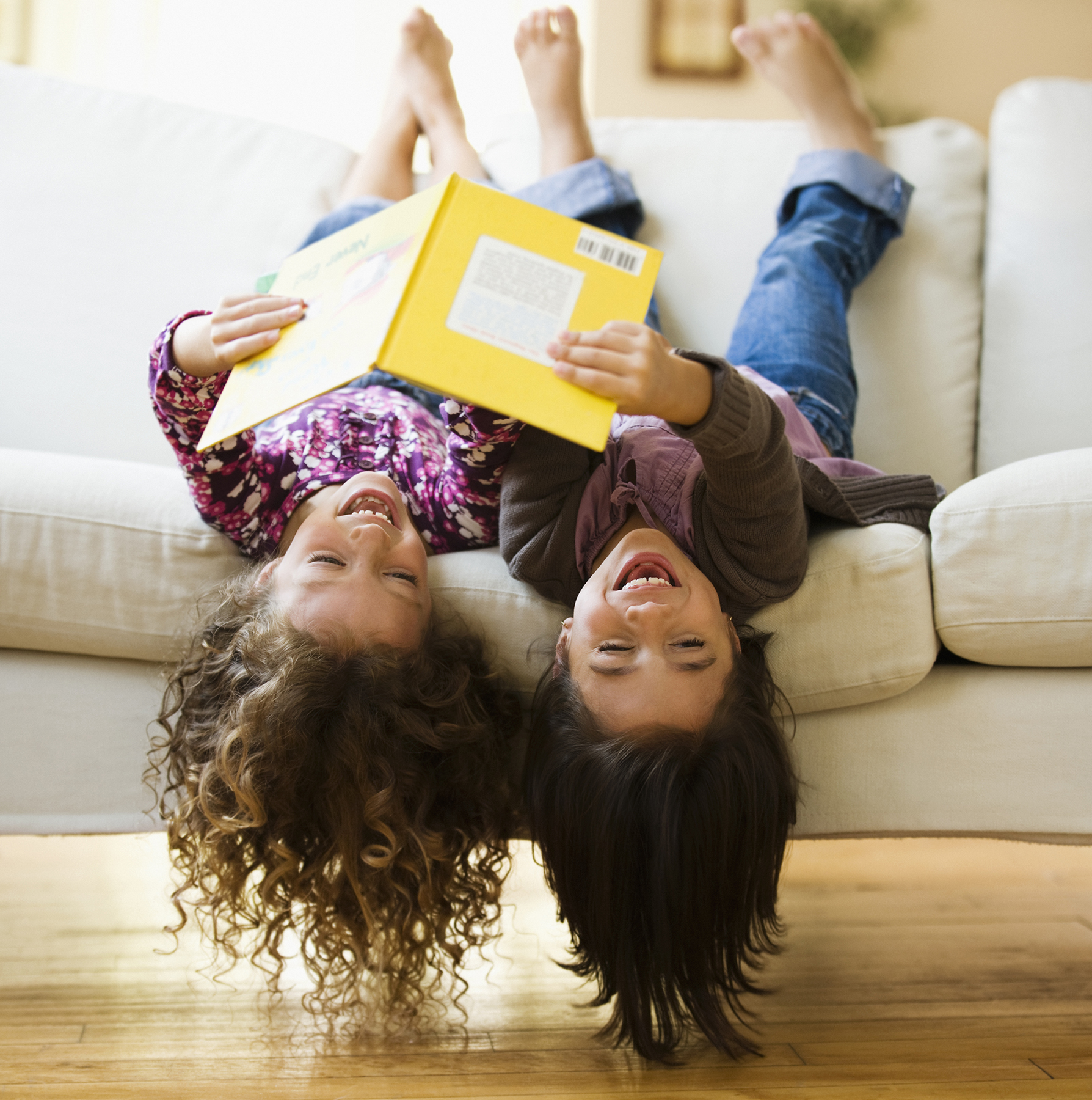 Girls upside down on sofa with book