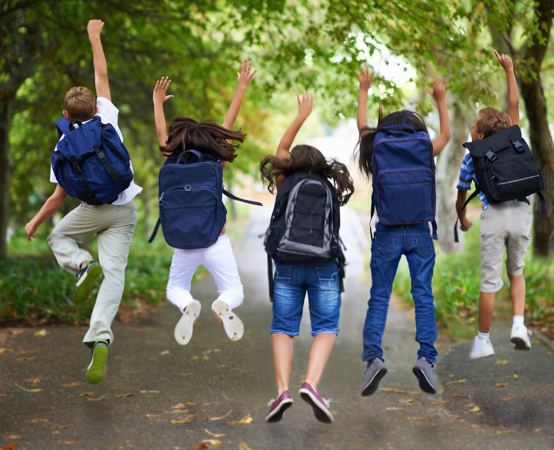 School Kids Wearing Backpacks Jumping in Air