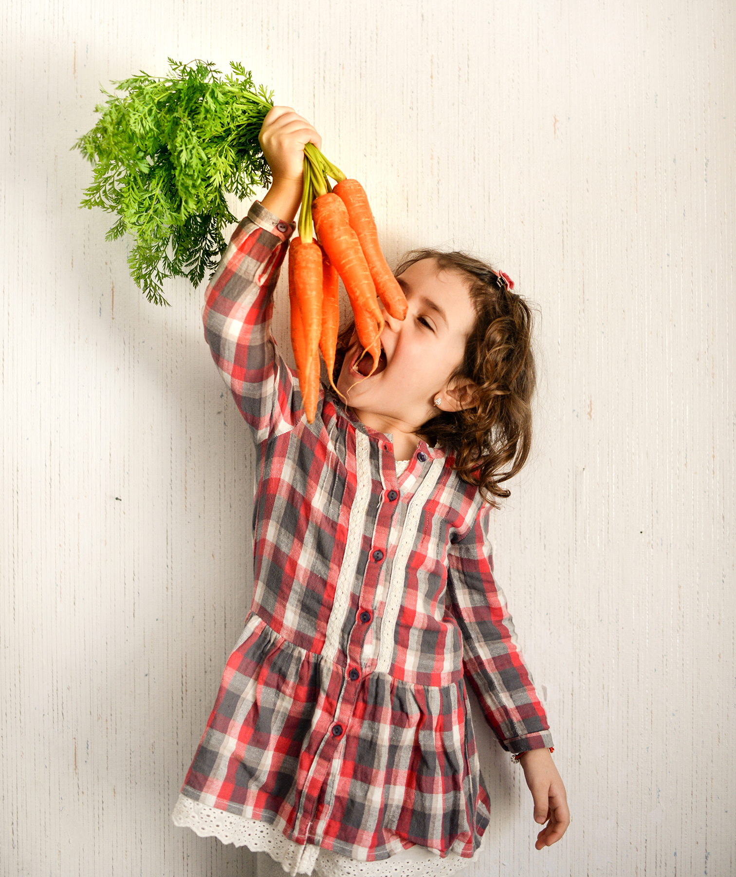 Little girl with bunch of carrots