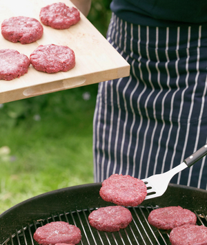 Raw meat being put onto a grill